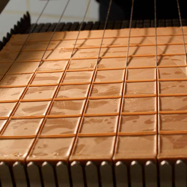 une grille qui découpe une plaque de chocolats pour La Boîte à biscuits