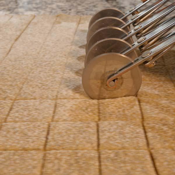 des roulettes découpent de la pâte à biscuit