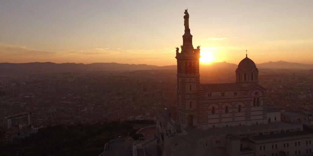 vue drone d'un coucher de soleil derrière Notre-Dame de la Garde à Marseille