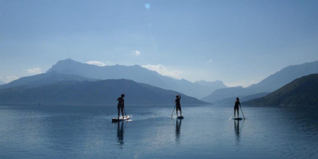trois personnes font du paddle sur le lac de Serre-Ponçon