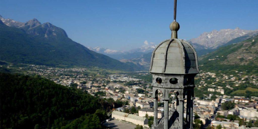 survol drone du clocher de l'église d'Embrun avec vue sur la vallée
