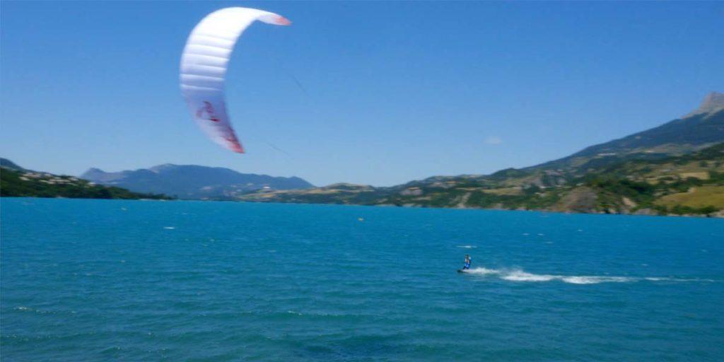 plan drone d'une personne qui fait du kitesurf sur le lac de Serre-Ponçon dans les Hautes-Alpes