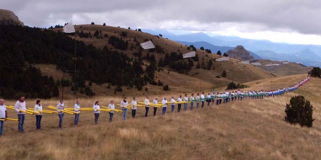 200 personnes en ligne tiennent chacune deux flûtes éoliennes sur la corniche de la montagne de Céüse