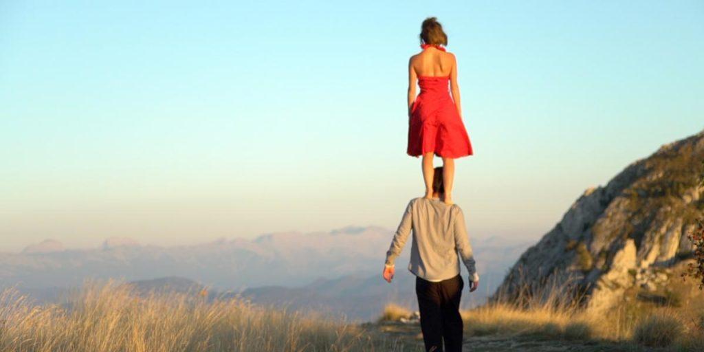 Justine, un femme en robe rouge est debout sur les épaules d'un homme, Frédéri