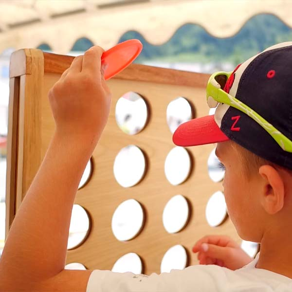 un petit garçon joue avec un jouet en bois au festival l'Echo des mots