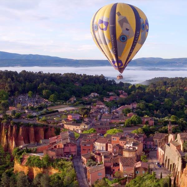 une montgolfière de L'Occitane en Provence survole un village du Lubéron