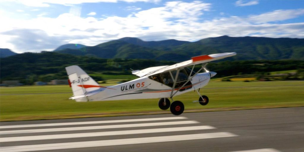 un ULM blanc décolle de la piste de l'aérodrome de Tallard dans les Hautes-Alpes
