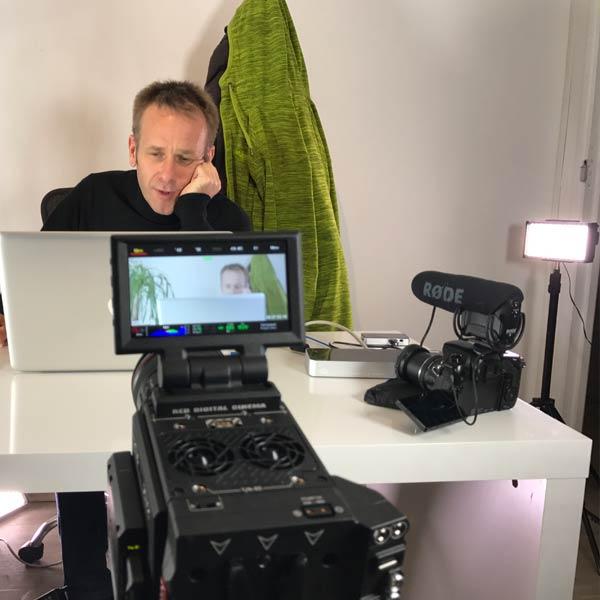 matériel de tournage et un homme qui consulte la météo sur son ordinateur