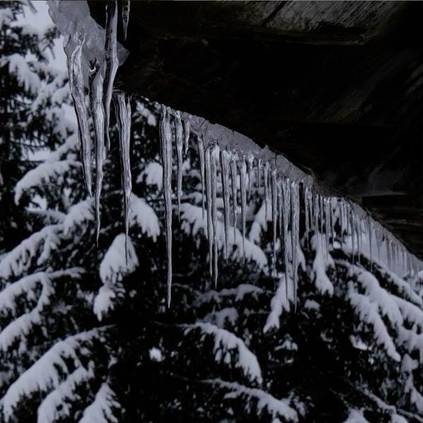 stalactites sur un rebord de toit dans une forêt enneigée des Hautes-Alpes