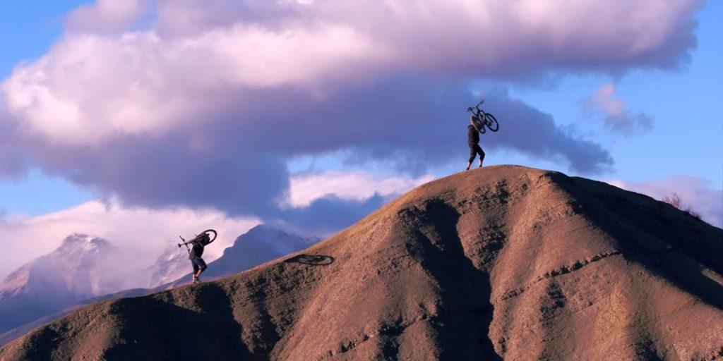 deux personnes portent leur VTT Lapierre en haut d'une colline