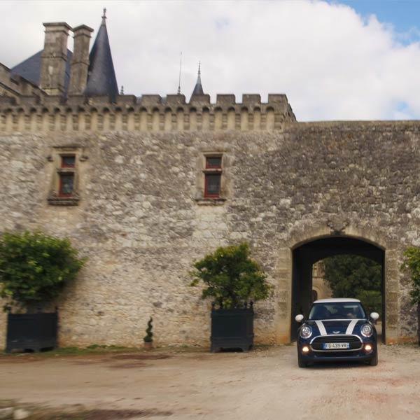 une voiture Mini Cooper bleue dans la cour d'un château de Dordogne