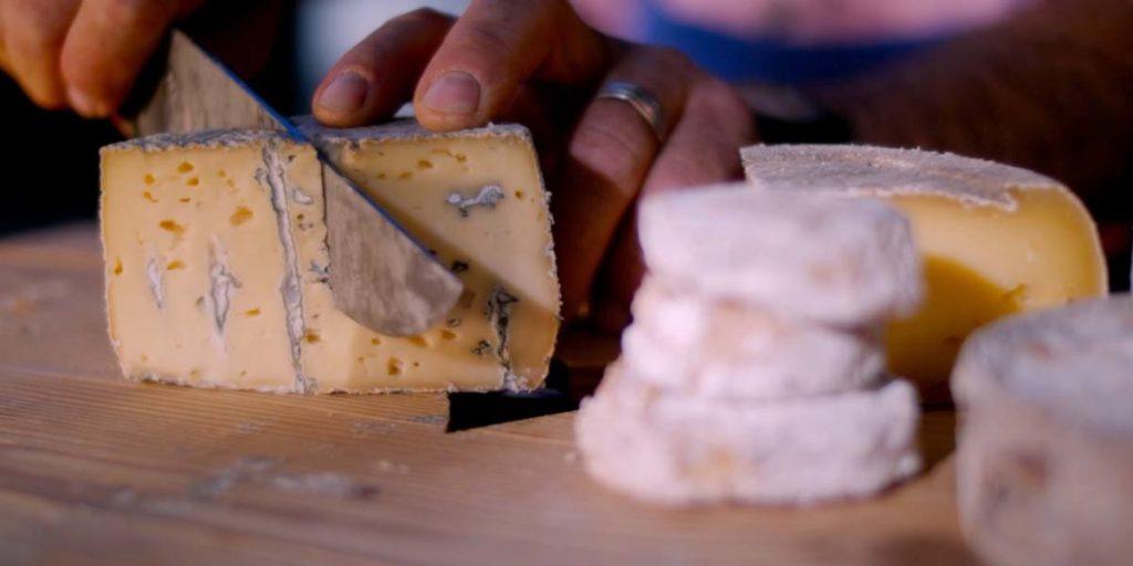 une personne coupe un fromage des Hautes-Alpes au salon de l'agriculture
