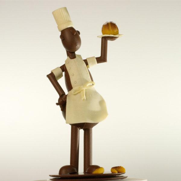 sculpture en chocolat représentant un bonhomme pâtisser portant un gâteau