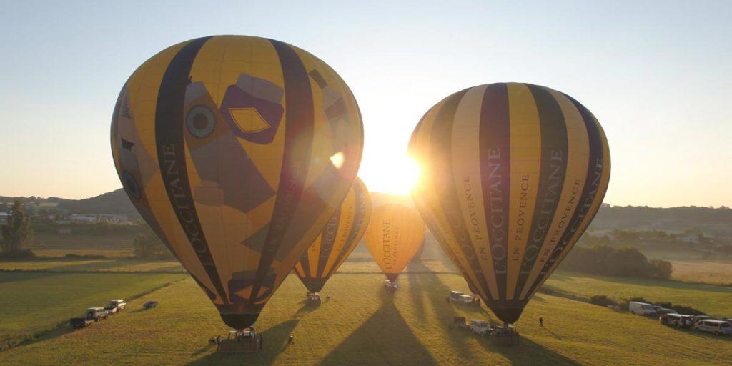 quatre montgolfières jaunes aux couleurs de l'Occitane en Provence sont sur le point de décoller, au petit matin