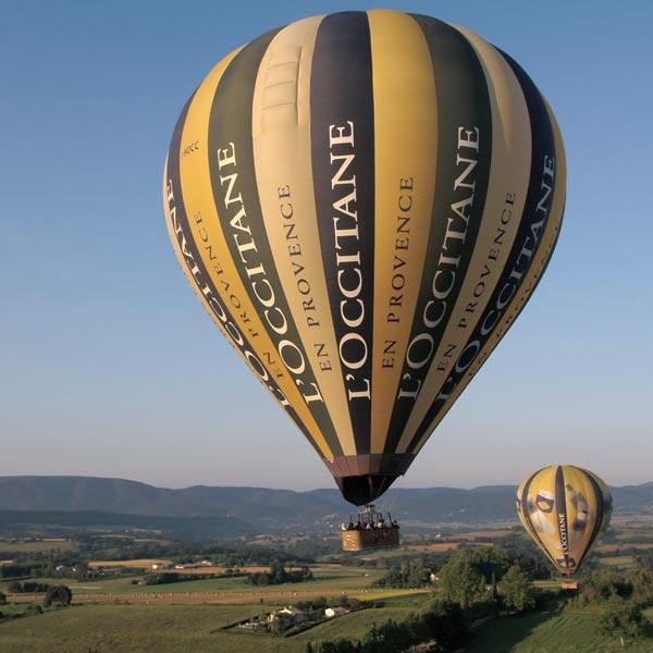 deux montgolfières jaunes et bleues aux couleurs de l'Occitane en Provence volent au dessus des champs