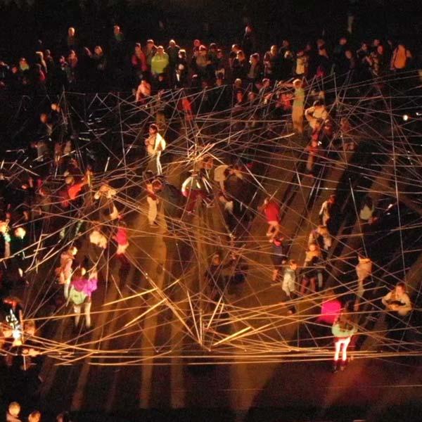Installation participative de nuit, le public essaie de démêler des fils
