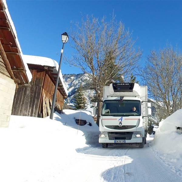 un camion blanc Alpagel effectue une livraison dans un village de montagne enneigé