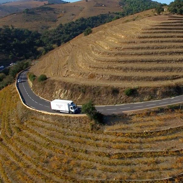 un camion blanc Alpagel roule sur une route de montagne l'été