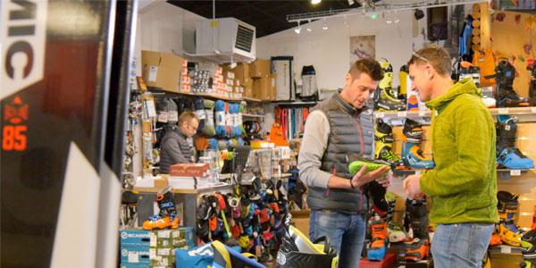 un employé renseigne un client sur des chaussures dans un magasin Approach
