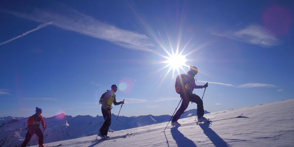 trois skieurs de randonnée grimpent au sommet des Orres lors d'une matinée ensoleillée