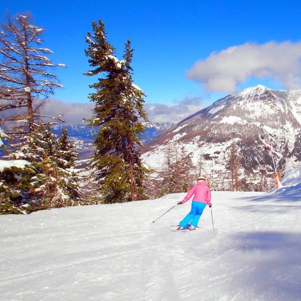 une skieuse descend une piste de ski aux Orres
