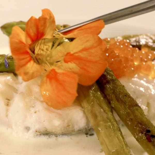 fleur orange posée délicatement sur un plat de poison et asperges au restaurant l'Auberge de la Méouge