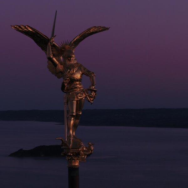 la statue de l'archange saint Michel au sommet de l'abbaye du Mont saint Michel, au crépuscule