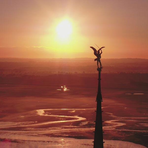 flèche de l'abbaye du mont saint Michel au coucher du soleil