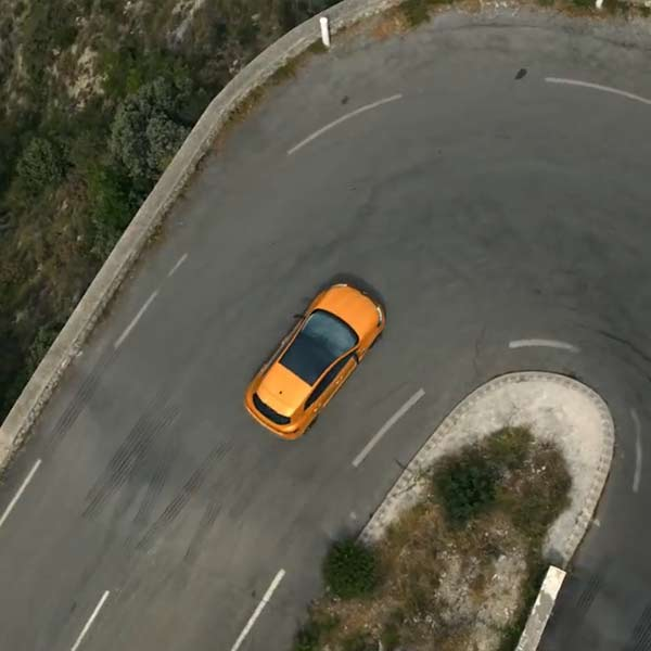 Plan drone au dessus de la Renault Megane R.S. à l'abord d'un virage en épingle